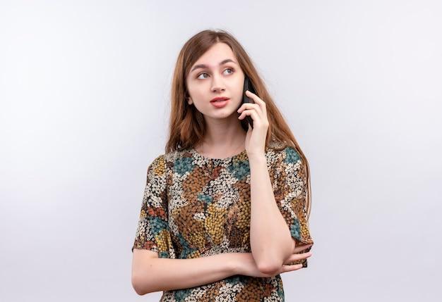 Giovane donna con i capelli lunghi che indossa abiti colorati sorridente mentre parla al telefono cellulare in piedi sul muro bianco