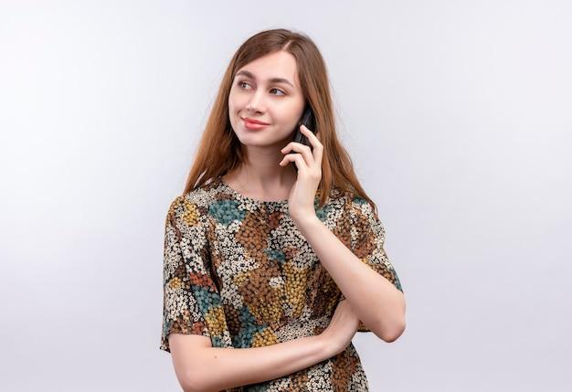 白い壁の上に立っている携帯電話で話しながら笑顔のカラフルなドレスを着て長い髪の若い女性