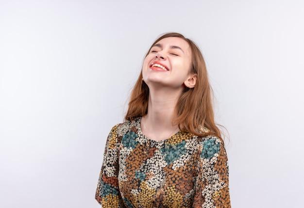 白い壁を笑って目を閉じて立っているカラフルなドレスを着て長い髪の若い女性