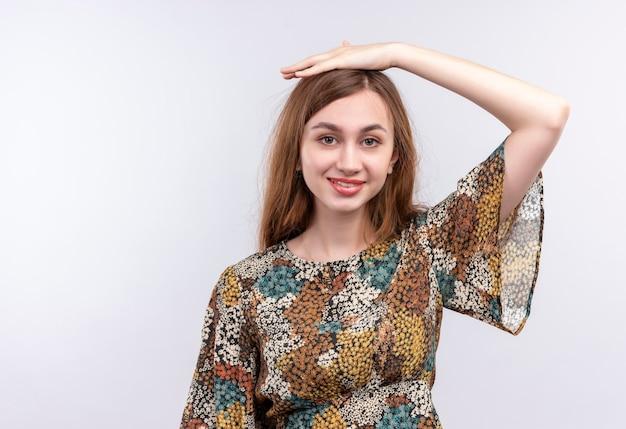 白い壁に笑みを浮かべて彼女の頭に手で立っているカラフルなドレスを着て長い髪の若い女性