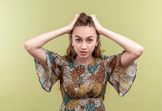 カラフルなドレスを着て長い髪の若い女性は、緑の壁の上に立っている頭に触れるストレスと欲求不満
