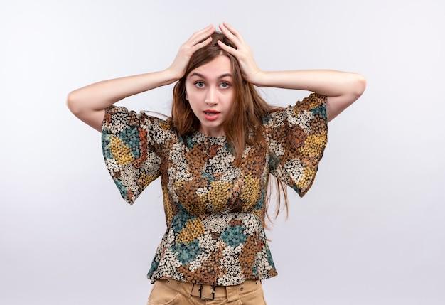 カラフルなドレスを着て長い髪の若い女性は、白い壁の上に立っている頭に触れるストレスと欲求不満
