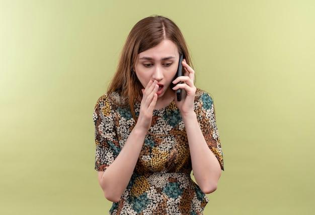 緑の壁の上に立ってショックを受けた携帯電話で話しているカラフルなドレスを着て長い髪の若い女性