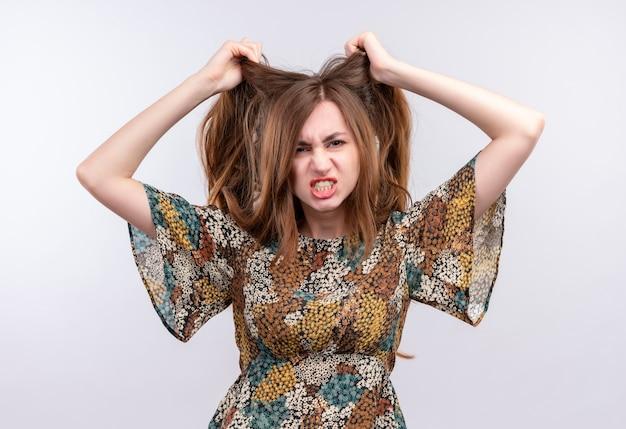 カラフルなドレスを着た長い髪の若い女性は、白い壁の上に立っている髪を引っ張る攻撃的な表情で非常に怒って欲求不満の叫び