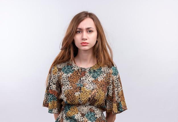 白い壁の上に立っている顔に悲しい表情で非常に見ているカラフルなドレスを着て長い髪の若い女性