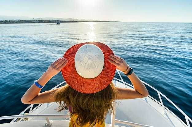 Young woman with long hair wearing yellow dress and straw hat standing on white yacht deck enjoying view of blue sea water.