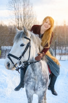 Young woman with long hair with horse in winter