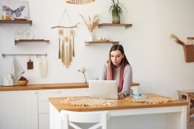 긴 머리를 가진 젊은 여자는 원격 교육, 집에서 노트북에서 원격으로 작동합니다. 프리랜서 작업. 온라인으로 학생들을 가르칩니다.