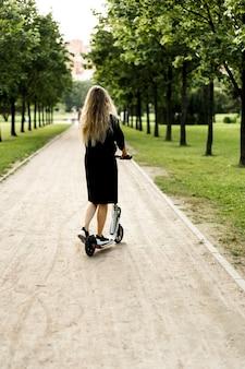Молодая женщина с длинными волосами на электрический скутер. девушка на электрическом самокате.
