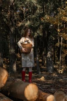 Молодая женщина с длинными рыжими волосами в льняном платье, собирающих грибы в лесу