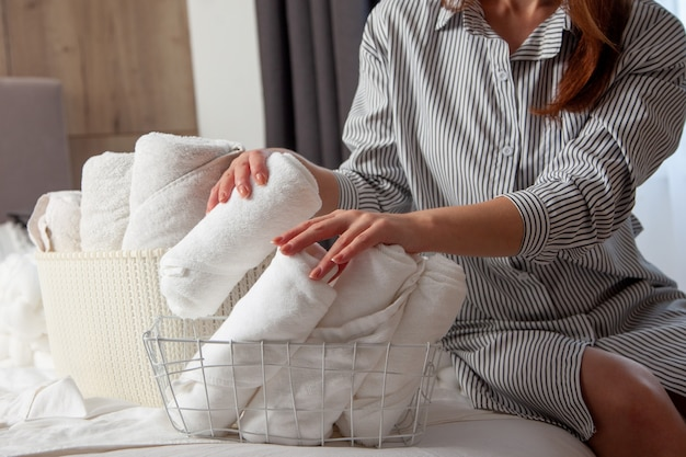 Young woman with long red hair is sitting on bed and folding clean white hand towels into mesh basket in bedroom. stack of roll up towels with copy space. neat and tidy linen. hypoallergenic textile.