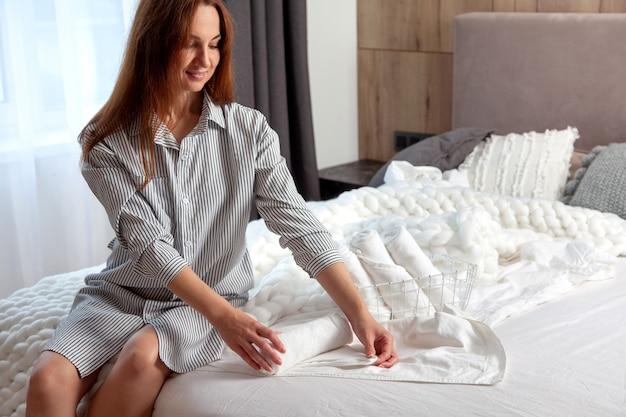 Молодая женщина с длинными рыжими волосами сидит на кровати и складывает чистые белые полотенца для рук в сетчатую корзину в спальне. стек рулонных полотенец с копией пространства. чистое и аккуратное белье. гипоаллергенный текстиль.