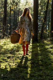 Young woman with long red hair in a linen dress gathering mushrooms in the forest