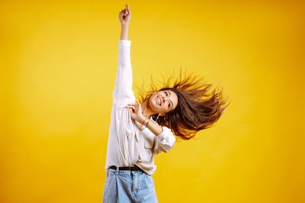 노란색에 포즈 흰 셔츠에 긴 물결 모양 머리를 가진 젊은 여자.
