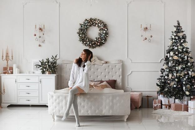 Молодая женщина с длинной волнистой прической и ярким макияжем в шерстяном свитере в оформленной на рождество спальне.