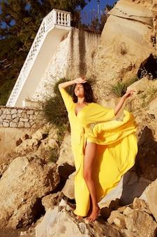 Молодая женщина с длинным желтым платьем позирует на открытом воздухе