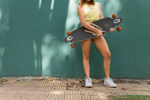 Young woman with longboard on green background