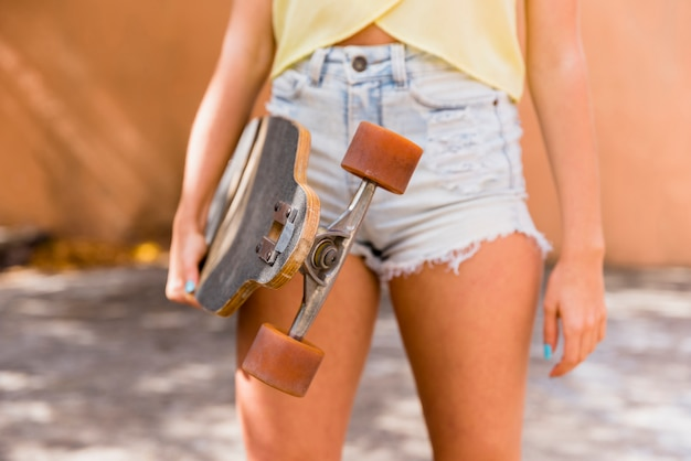 Young woman with longboard on street