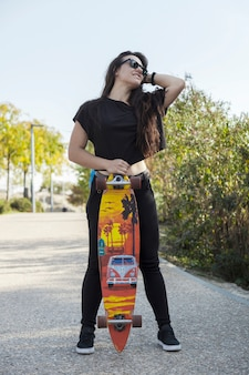 Young woman with longboard on sunny day