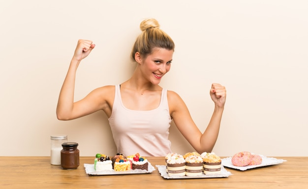 Young woman with lots of different mini cakes in a table celebrating a victory