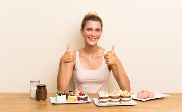 Young woman with lots of different mini cakes in a table giving a thumbs up gesture