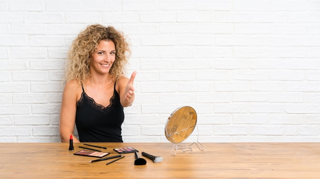 Young woman with lots of makeup brush in a table handshaking after good deal