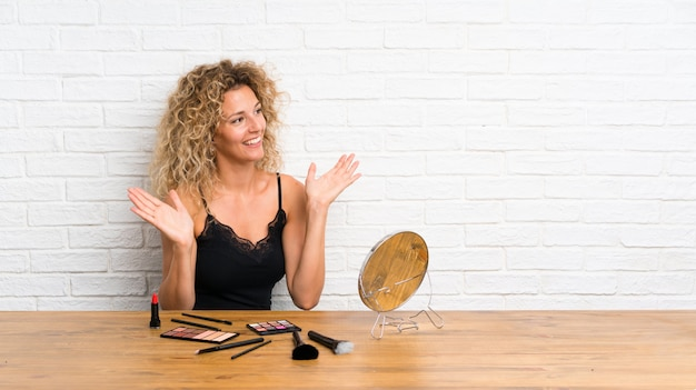 Young woman with lots of makeup brush in a table with surprise facial expression