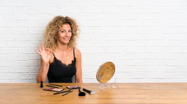 指でokの標識を示すテーブルに化粧ブラシの多くを持つ若い女性