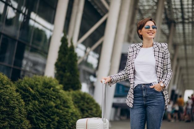Giovane donna con bagagli in aeroporto in viaggio