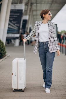 Young woman with luggage at airport travelling