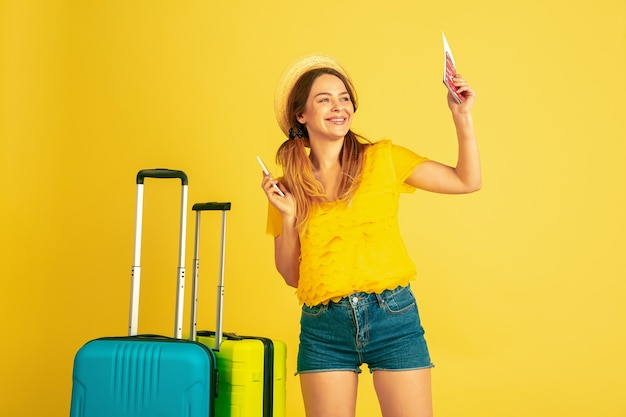 Молодая женщина с багажом и билетами на самолет