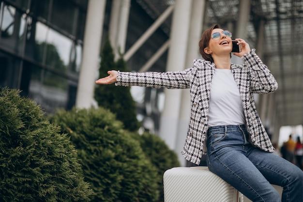 Молодая женщина с багажом в аэропорту путешествует и разговаривает по телефону