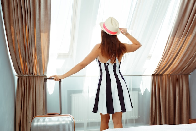 Young woman with luggage in hotel room