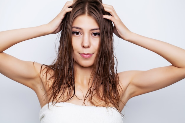 Young woman with luxurious hair applies conditioner for hair care