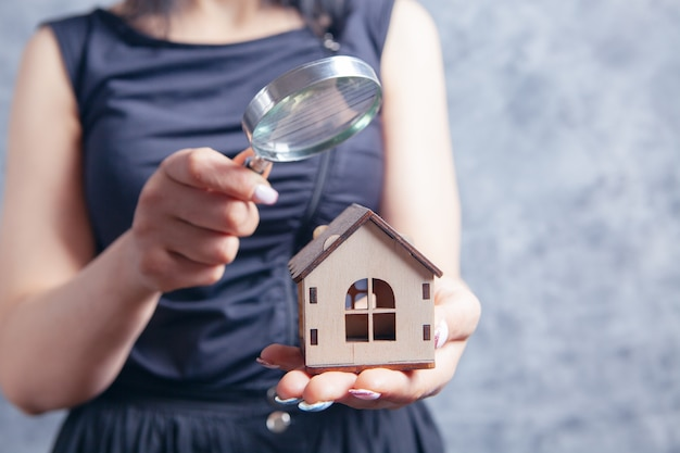 Young woman with a magnifying glass looks at the house on a gray background