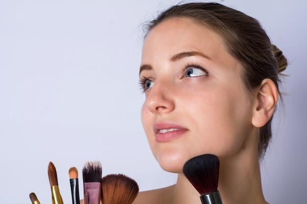 化粧筆を持つ若い女