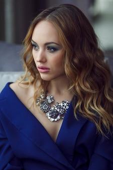 青いスーツで化粧をした若い女性、自然光の中で銀のネックレスを着用