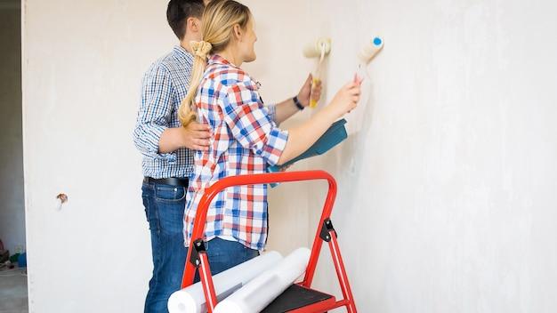 Молодая женщина с мужчиной делает ремонт и красит все дома.