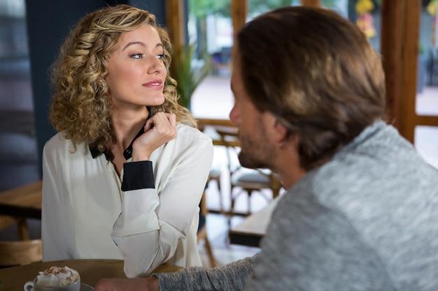 Молодая женщина с мужчиной, сидящим за столом в кафе