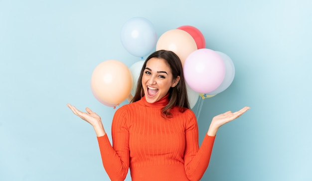 Young woman with many balloons isolated on blue