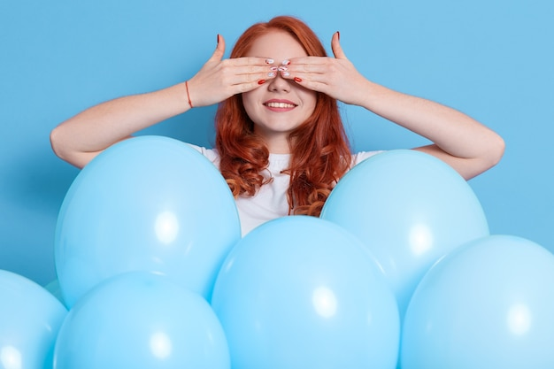 Young woman with many blue balloons over isolated color wall, covering eyes by hands and smiling, having surprise on her birthday, european lady expressing positive emotions on holiday.