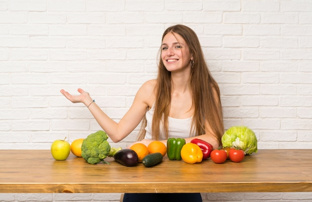 Young woman with many vegetables holding copyspace imaginary on the palm