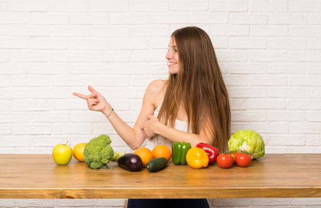 Young woman with many vegetables pointing finger to the side