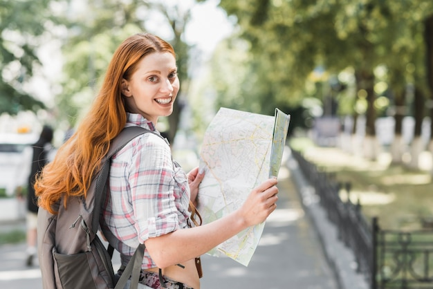 Young woman with map in park