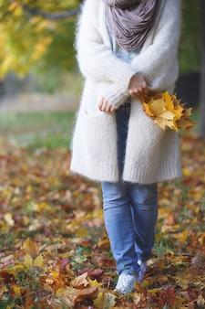 Молодая женщина с кленовыми листьями на фоне осеннего заката