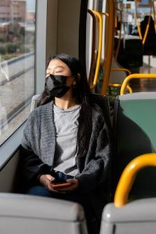 Giovane donna con la maschera in autobus