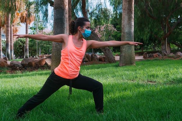 新しい通常の公園でヨガの姿勢をしているマスクを持つ若い女性