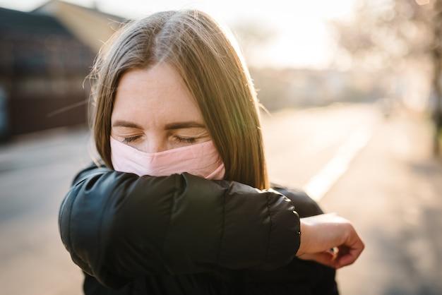 Молодая женщина с маской во время пандемического кашля covid-19 на улице