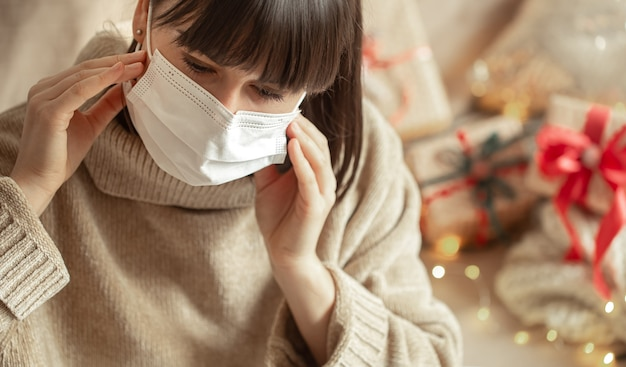 Young woman with a mask on her face in a cozy beige sweater on a blurred wall with bokeh. the concept of winter holidays during the coronavirus.