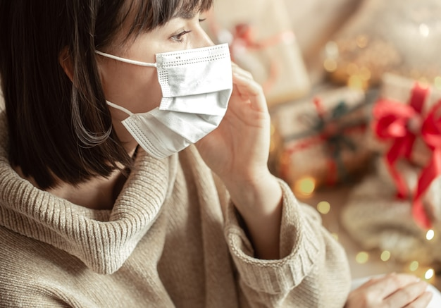Young woman with a mask on her face in a cozy beige sweater. the concept of christmas during the coronavirus.